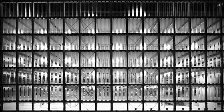 Ein Parkhaus von außen. Stahlträger in der Fassade und Betonträger innen formen Quadrate, Rechtecke, Streifen.