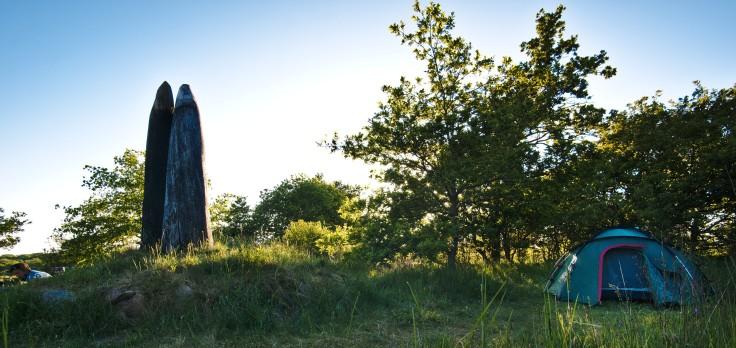 Links eine Person am Kochen neben einer Skulptur, die zwei stehende Hörner symbolisiert, rechts ein Zelt.