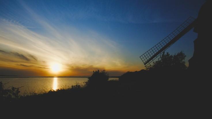 Ein Sonnenuntergang über der Ostsee, mit der Silhouette einer Windmühle im Vordergrund.