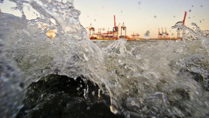 Eine Welle kommt genau auf den Betrachter zu und füllt das Bild aus. Im Hintergrund Hafenkräne.