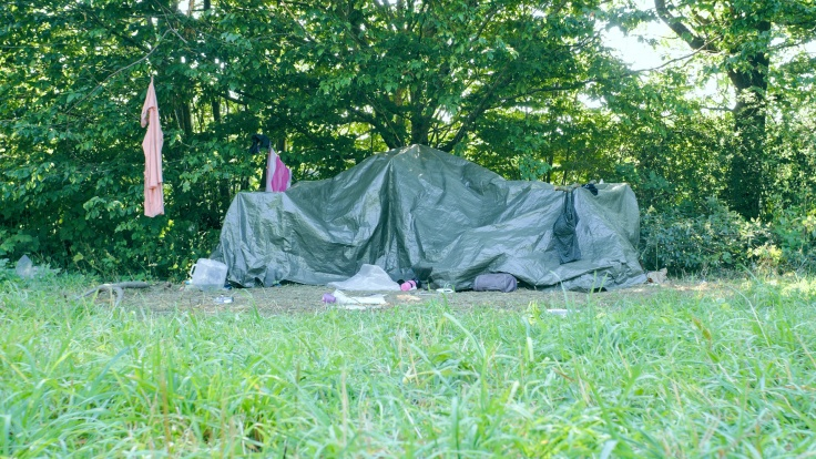 Eine mit Folie abgedeckte Übernachtungsstätte. In den Büschen drumrum hängen Handtücher, T-Shirts und ein Badeanzug zum Trocknen, im Gras ringsrum sind Gegenstände wie z.B. ein Wasserkanister verteilt.