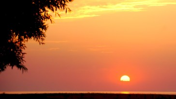 Ein schmaler Streifen Land und Meer am unteren Bildrand, ansonsten orange bis rosa leuchtender Himmel mit untergehender Sonne.