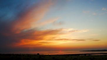 Ein Sonnenuntergang am Meer. Die Sonne ist schon halb hinter dem Horizont, die Wolken leuchten in spektakulären Mustern und Farben.